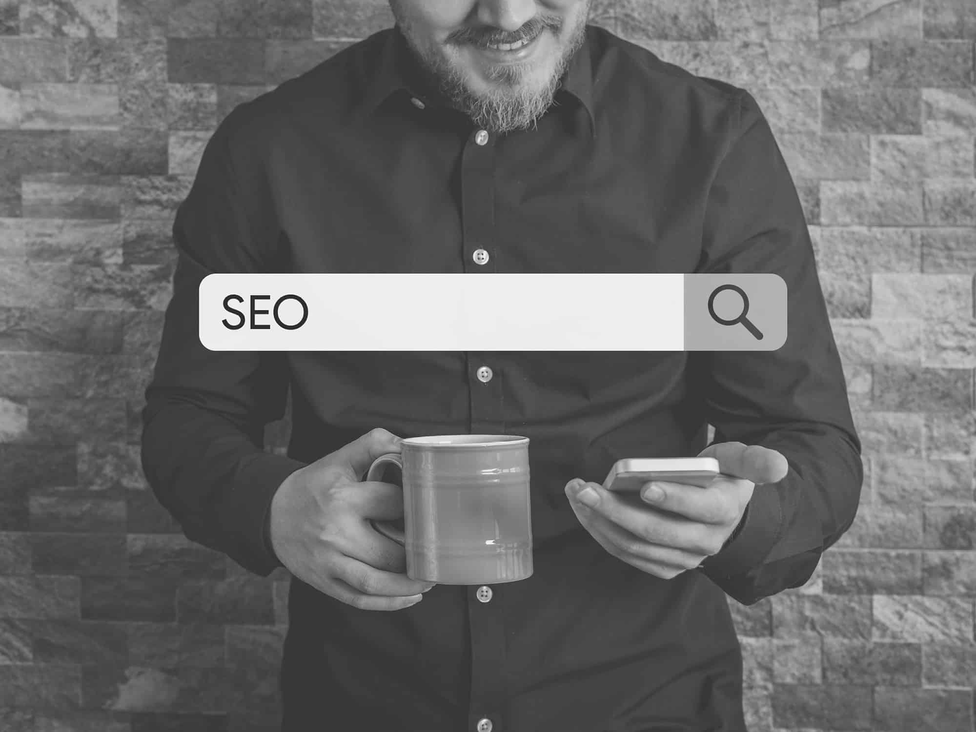 man on phone with search box reading SEO black and white image