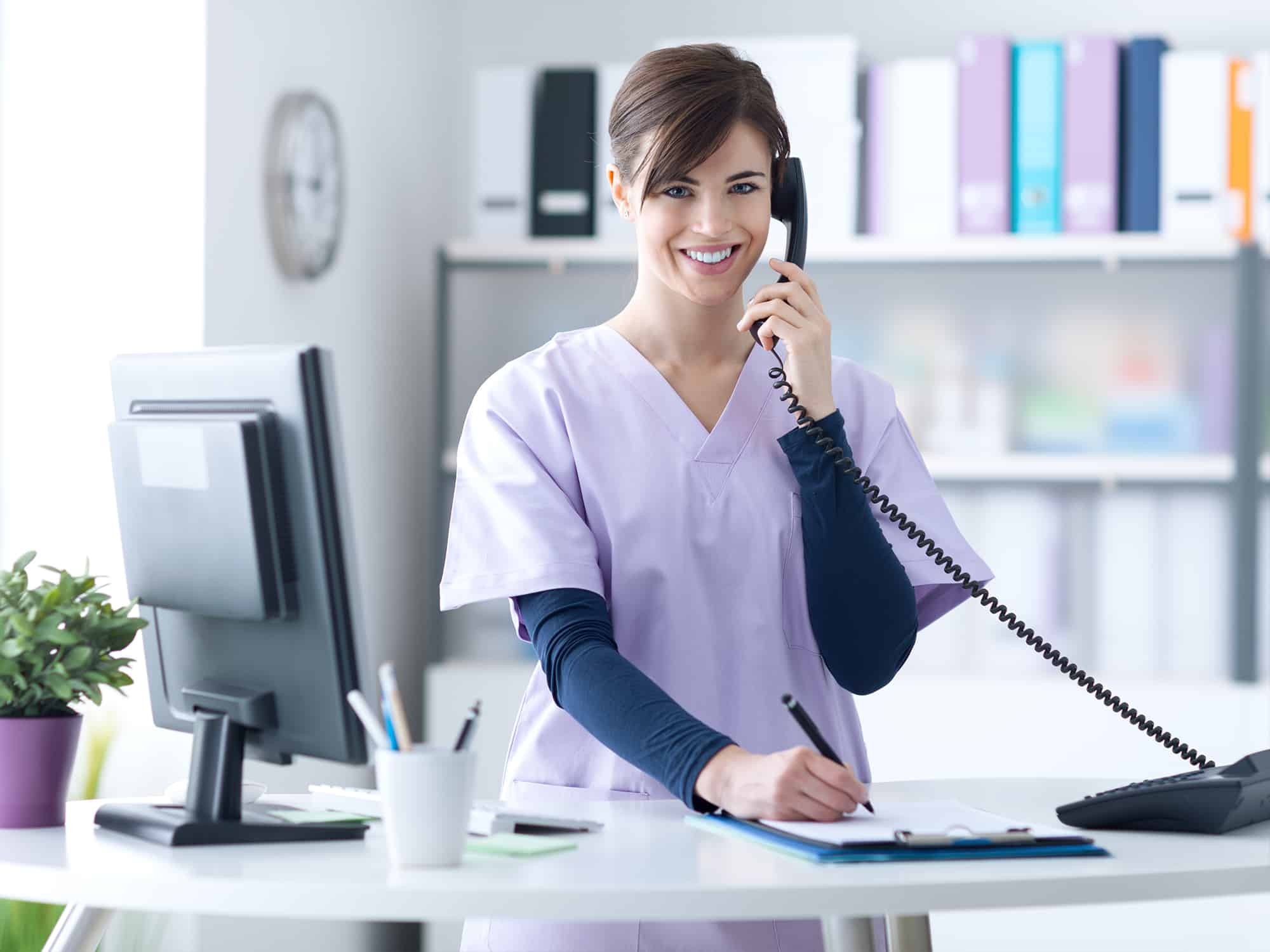 dental assistant in scrubs answers the phone