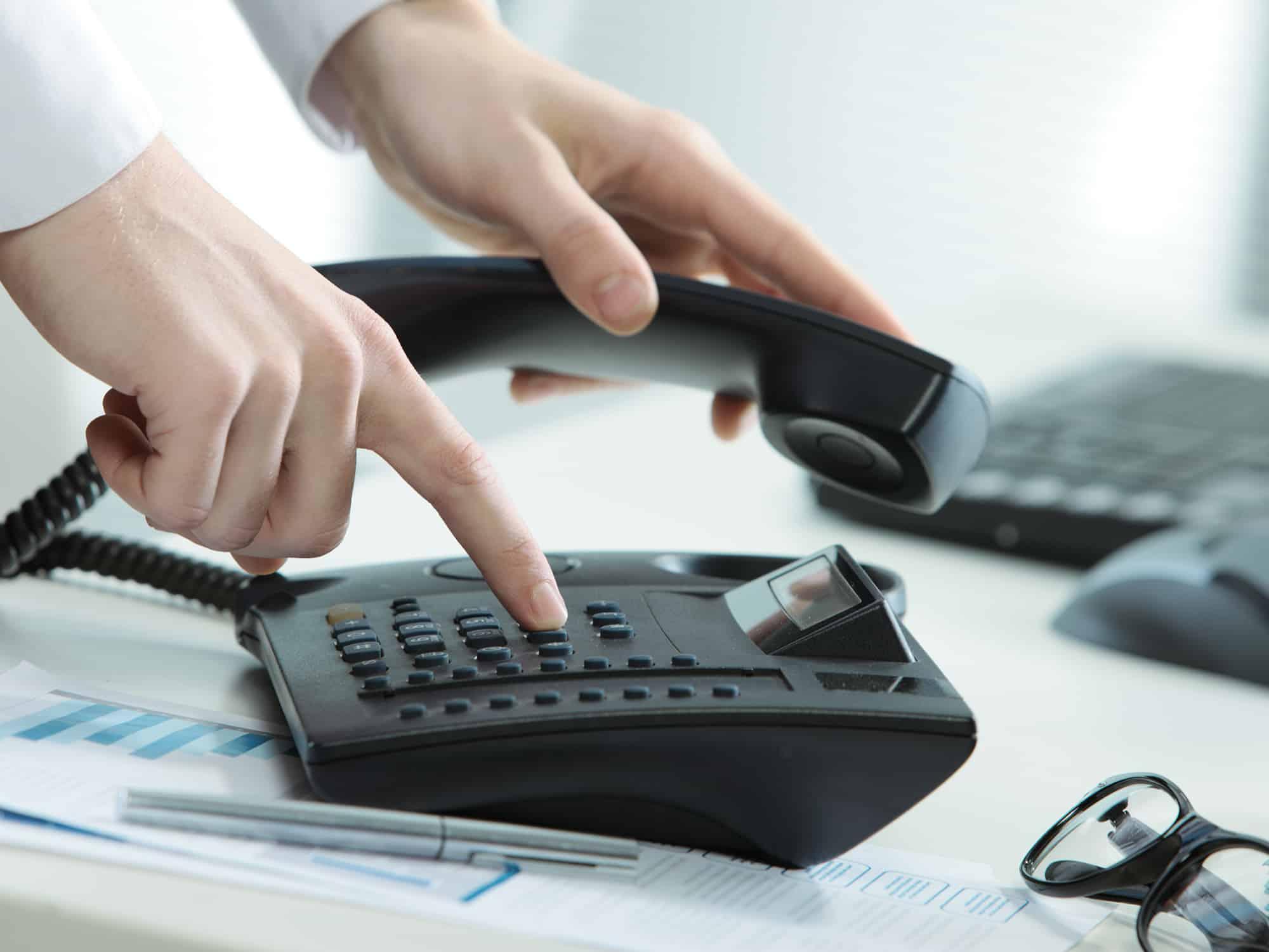 man dialing office phone