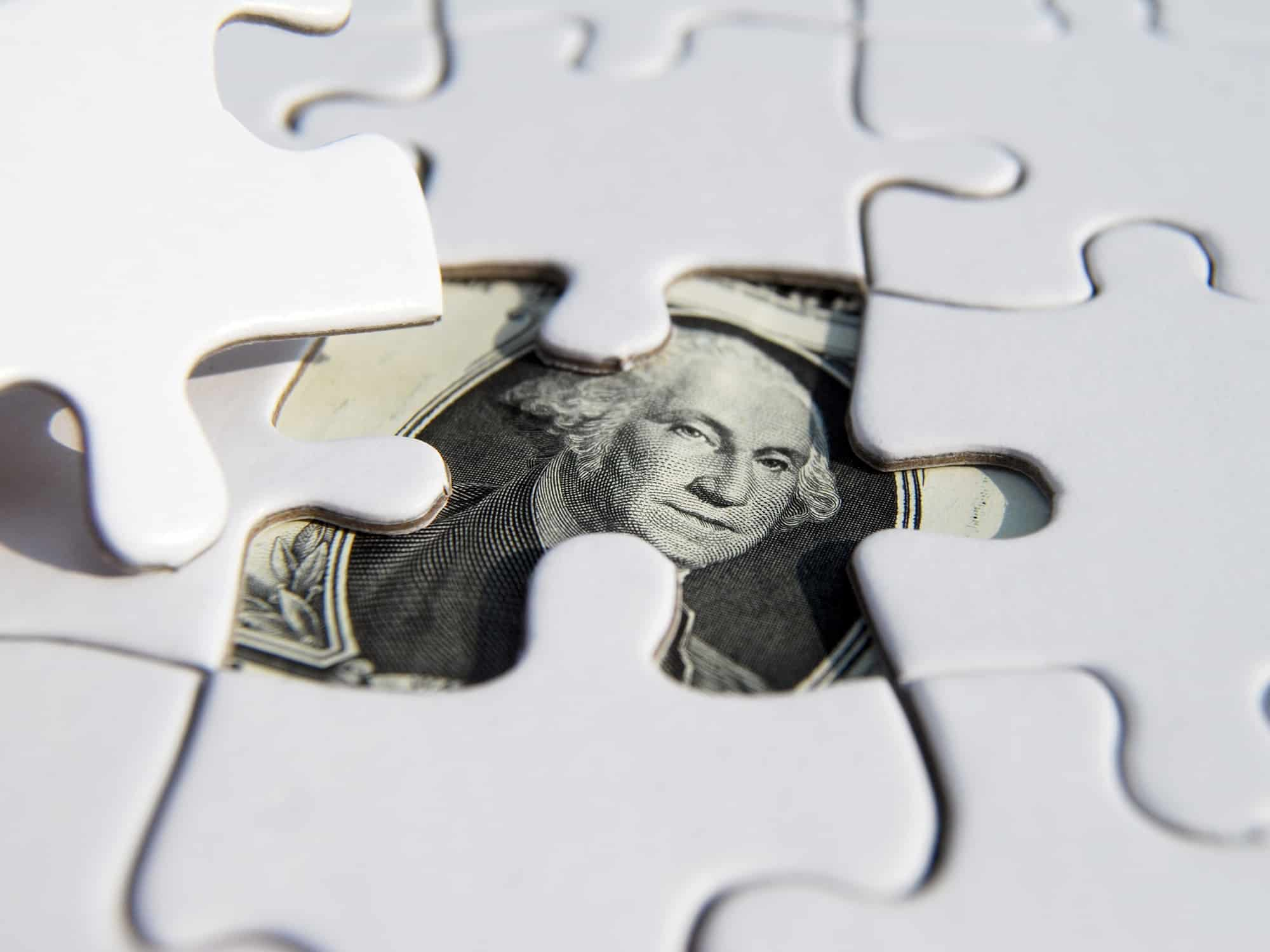 dollar bill under puzzle pieces